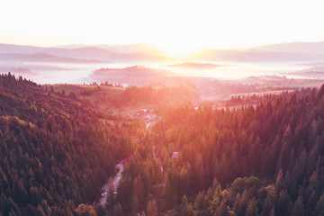 aerial view of sunset over mountains with forest and river © phpetrunina14