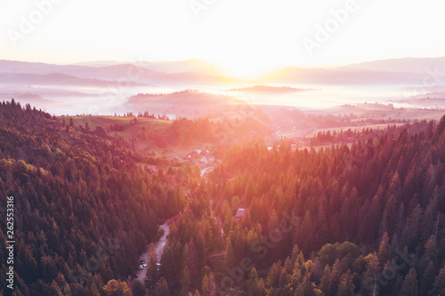 aerial view of sunset over mountains with forest and river
