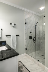 Modern bathroom with glass shower and marble tile.
