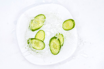 cucumbers and water splashes in a plate on a white background