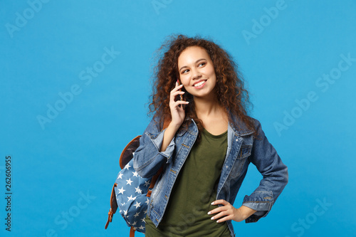 Young african american girl teen student in denim clothes, backpack hold phone isolated on blue wall background studio portrait. Education in high school university college concept. Mock up copy space