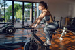 Young girl on the exercise bike is training in the fitness room