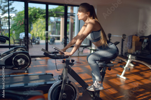 canvas print picture  Young girl on the exercise bike is training in the fitness room