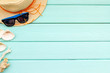 Quadro Summer travaling to the sea with straw hat, sun glasses, shells on mint green wooden background top view mock up