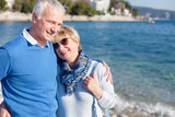 Senior couple is laughing, smiling at sea beach outdoor. Happy man and woman are hugging, traveling, enjoying retirement. Concept of wellbeing, love, happiness. Lifestyle, authentic moments, emotions.