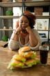 Serious international female person staring at hamburgers