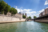 River Seine, bridge and Cathedral Notre Dame de Paris, France, Europe. Summer sunny day with blue sky. Water and embankment