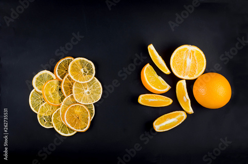 canvas print picture dried and raw sliced oranges on dark background