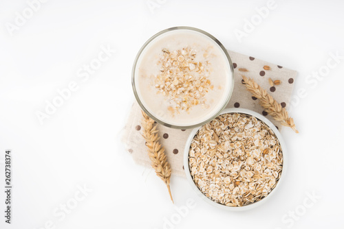 Glass of oat milk and grains in white bowl © dimasobko