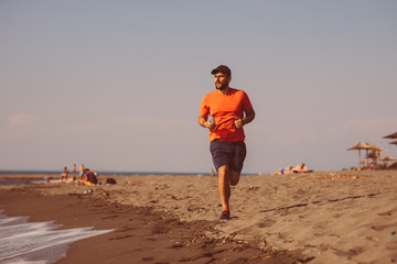Young man jogging on the beach by the sea