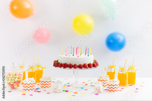 party food and festive concept - birthday cake with candles and strawberries, drinks, popcorn and marshmallow on table © Syda Productions