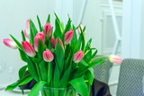bouquet of pink tulips in a glass vase on a white window background