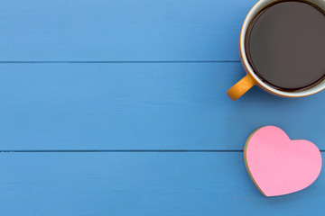 Coffee cup and pink love heart top view on blue wood table minimal background
