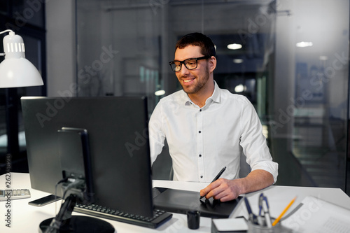 Leinwandbild Motiv business, graphic design and technology concept - designer or businessman in glasses with computer and pen tablet working at dark night office