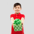 birthday, childhood and people concept - smiling little boy in red polo t-shirt with gift box over grey background