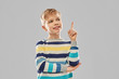 childhood, expressions and people concept - little boy in striped pullover pointing finger up over grey background