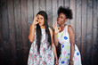 Two black african girlfriends at summer dresses posed against dark wooden background and showing okay fingers sign.