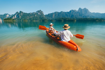 Mother and son floating on kayak together on Cheow Lan lake in Thailand