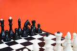 Symbol of competition. Chess board and chess figures on orange background top view copy space