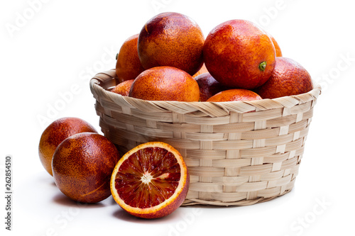 Ripe red oranges in wicker basket isolated on white © lena_zajchikova