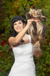 Beautiful and happy brunette young bride in the fashionable dress with the cute surprised cat in her hands