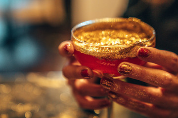 Golden cocktail glass at the bar. Young women's hand holding a martini glass with a golden stardust on top of it.