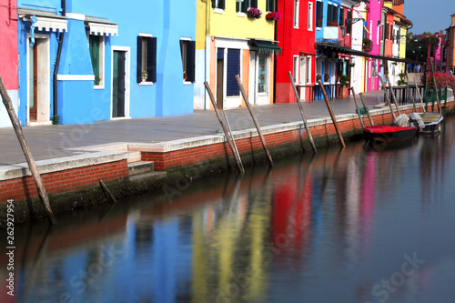 Navigable canal on Burano Island near Venice in Italy and the fa