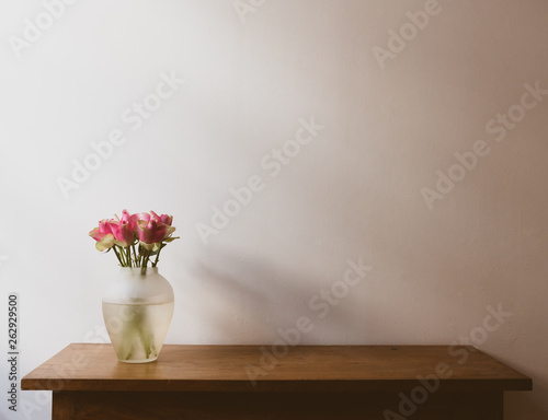 Pink and cream roses on wooden oak side table against neutral wall with moody lighting - warm matte filter effect and selective focus