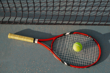red tennis racquet and a tennis ball in front of the court