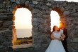 Beautiful romantic wedding couple posing in old window with view at sea