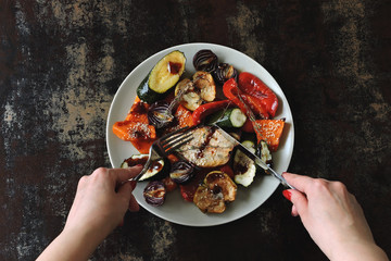 Baked vegetables and fruits with sesame on the plate. Vegan food. Healthy diet. Shabby background. Stylish vegan lunch.
