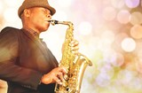 Close-up man playing on saxophone on blurred background
