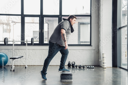 overweight man with towel exercising on step platform at sports center © LIGHTFIELD STUDIOS