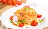 Spaghetti pasta with cherry tomatoes and basil leaves on white plate