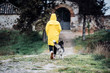 Pretty blonde woman and yellow raincoat walking with Siberian Husky dog.
