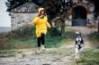 Pretty blonde woman and yellow raincoat running with Siberian Husky dog.