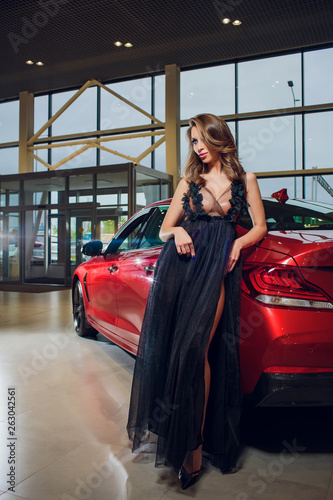 Portrait of chic young Brunettes with a sexual chest near the car. - 263042561