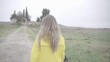Pretty blonde woman with yellow raincoat walking in the rain.