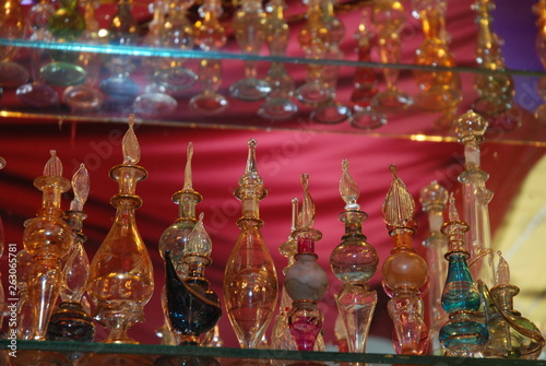 shelves with glass oriental bottles for oils © Evdoha