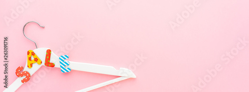 White hangers with sale text on pink background