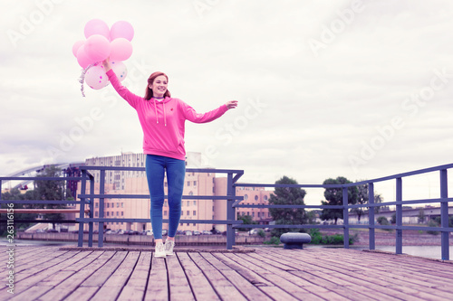 Beaming ginger woman walking on wooden pier with balloons © Viacheslav Iakobchuk