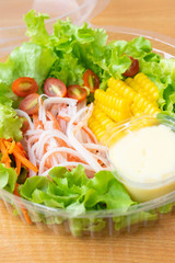 Crab sticks salad with corn,green oak, onion and tomato in clean plastic box.