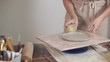Female artisan is making clay plate by hands in her studio, rotating blank