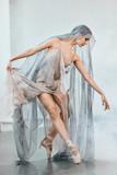Beautiful dark-haired Arabian female dancer dancing in grey transparent costume with cape on head in white studio