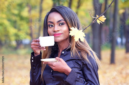 Beautiful young African woman drinking coffee from a white Cup on the background of autumn leaves in the Park