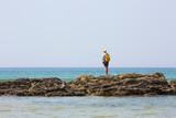 Pêcheur à la ligne sur un rocher
