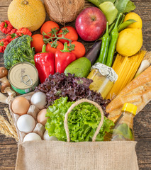 Many vegetables and fruits in the shopping bag on the table