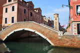 Canal and bridge in quieter area of Venice with wall and tower of the Arsenale .