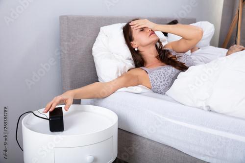 Woman Sleeping On Bed Turning Off Alarm Clock © Andrey Popov