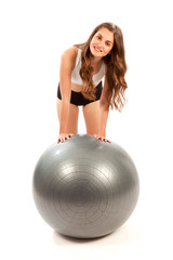 Young woman is resting after exercising with a big gray gymnastic ball. © fesoj
